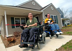 [Photo: The Keens on wheelchair in front of their new home]