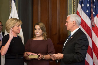 [Vice President Mike Pence delivering the oath of office Pamela Hughes Patenaude with her daughter Meghan Patenaude (holding the bible). Official White House photo: Joyce Boghosian]