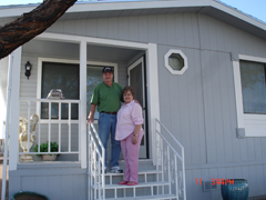 [Photo 4: Mr. and Ms. Hoover smiling in front of home]