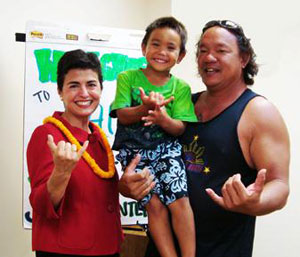 [Photo: Ophelia Basgal with a local father and son make the traditional Hawaiian Shaka gesture]