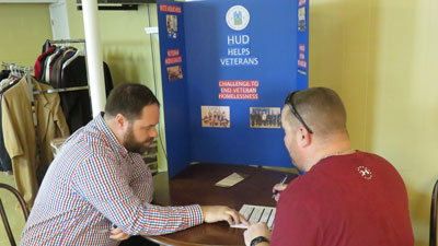 [Photo 1: David Railey, HUD Kentucky Office Senior Management Analyst, helps a veteran fill out an application for permanent housing]