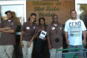 [Photo 2: Employees of the new First Choice Market are on hand to greet visitors during the celebration on June 12, 2012.]